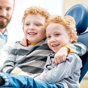 Two young boys smiling in dental chair