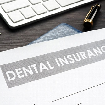 Dental insurance form and money on desk.