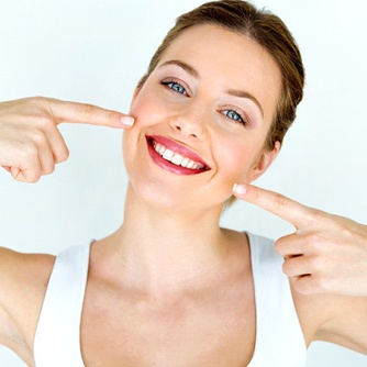 Woman pointing to her healthy smile.