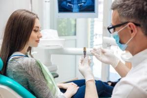 Dentist showin patient dental implant model