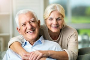 Smiling older couple with dental implants in Farmington