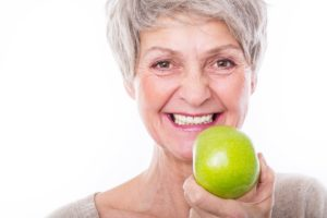 Woman using denture adhesive holding an apple