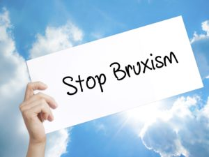 """Hand holding """"stop bruxism"""" sign"""